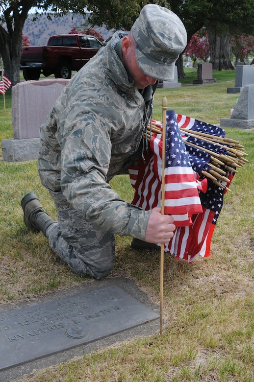 U.S. Air National Guard Staff Sgt. Jared Nanneman, 173rd Fighter Wing, places a flag on the graves of local veterans at Mount Calvary Cemetery in Klamath Falls, Ore. May 23, 2013.  Members of the 173rd Fighter Wing spent their morning placing flags in honor of Memorial Day.  (U.S. Air National Guard photo by Master Sgt. Jennifer Shirar) RELEASED