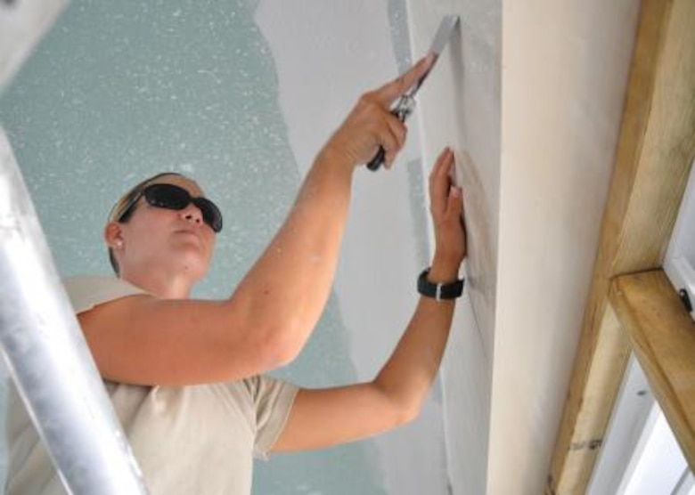 Senior Airman Stephanie Cannon, medical technician from the 92nd Medical Operations Squadron removes excess texture coating from the walls of Crooked Tree Government Primary School May 24, 2013. Civil Engineers from both the U.S. and Belize are constructing various structures at schools throughout Belize as part of an exercise called New Horizons. Building these facilities will support further education for the children of the country and provide valuable training for U.S. and Belizean service members. (U.S. Air Force photo/Capt. Holly Hess)
