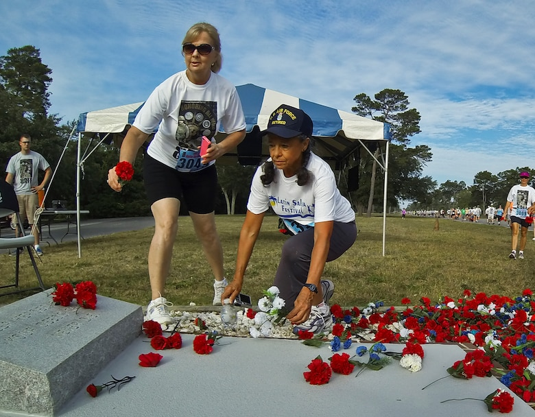 Joni LaFlamme (left) stops to honor the veterans by placing a flower on the memorial during the 28th annual Gate-to-Gate Run May 27 at Eglin Air Force Base, Fla. More than 1,500 people participated in the Memorial Day race.  Many of the runners paid their respects by dropping off flowers in front of the All Wars Memorial as they raced by.  (U.S. Air Force photo/Samuel King Jr.)
