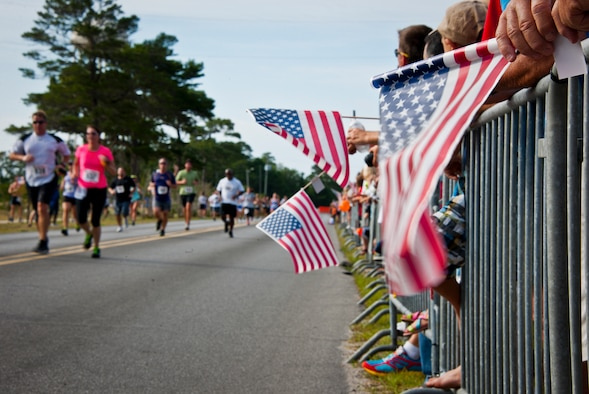 Flags were waved as the runners sprinted to the finish line at the 28th annual Gate-to-Gate Run May 27 at Eglin Air Force Base, Fla. More than 1,500 people participated in the Memorial Day race.  Many of the runners paid their respects by dropping off flowers in front of the All Wars Memorial as they raced by.  (U.S. Air Force photo/Samuel King Jr.)