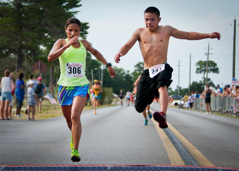 Thais Gutierrez and Matthew Espinoza leap to try and cross the finish line first during the 28th annual Gate-to-Gate Run May 27 at Eglin Air Force Base, Fla. More than 1,500 people participated in the Memorial Day race.  Many of the runners paid their respects by dropping off flowers in front of the All Wars Memorial as they raced by.  (U.S. Air Force photo/Samuel King Jr.)