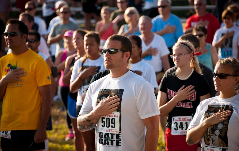 Everyone in the crowd, including Dathan Nordheim (middle), held their hand to their heart or stood at attention during the National Anthem at the 28th annual Gate to Gate Run May 27 at Eglin Air Force Base, Fla.  More than 1,500 people participated in the Memorial Day race.  Many of the runners paid their respects by dropping off flowers in front of the All Wars Memorial as they raced by.  (U.S. Air Force photo/Samuel King Jr.)