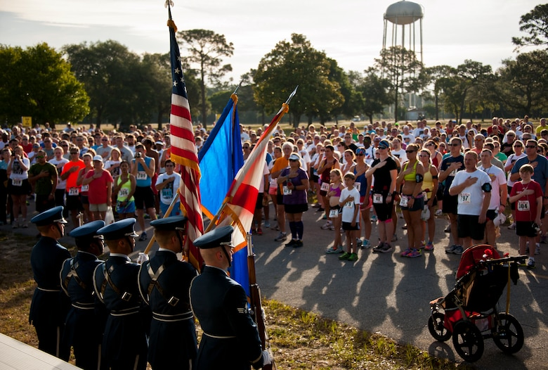 Everyone in the crowd held their hand to their heart or stood at attention during the National Anthem at the 28th annual Gate to Gate Run May 27 at Eglin Air Force Base, Fla.  More than 1,500 people participated in the Memorial Day race.  Many of the runners paid their respects by dropping off flowers in front of the All Wars Memorial as they raced by.  (U.S. Air Force photo/Samuel King Jr.)