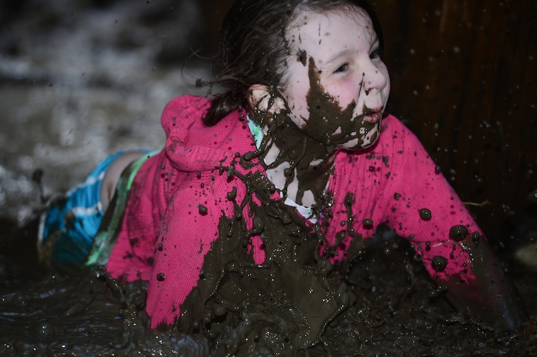 SPANGDAHLEM AIR BASE, Germany - Jaden Pelland, daughter of U.S. Air Force Senior Airman Jordan Williams, 606th Air Control Squadron, client system technician from Missoula, Mont., falls into a mud puddle during an obstacle during the Tier II Saber Sprint May 24, 2013. Pelland was the youngest and smallest participant in the Tier II Saber Sprint and was recognized during the closing ceremony. (U.S. Air Force photo by Staff Sgt. Christopher Ruano/Released)