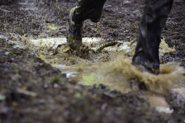 SPANGDAHLEM AIR BASE, Germany - Tier II Saber Sprint participants run through mud-filled trails May 24, 2013. More than 130 people participated in the third annual Tier II Saber Sprint. Private organizations from around the base worked together to build the obstacles for runners. (U.S. Air Force photo by Airman 1st Class Kyle Gese/Released)
