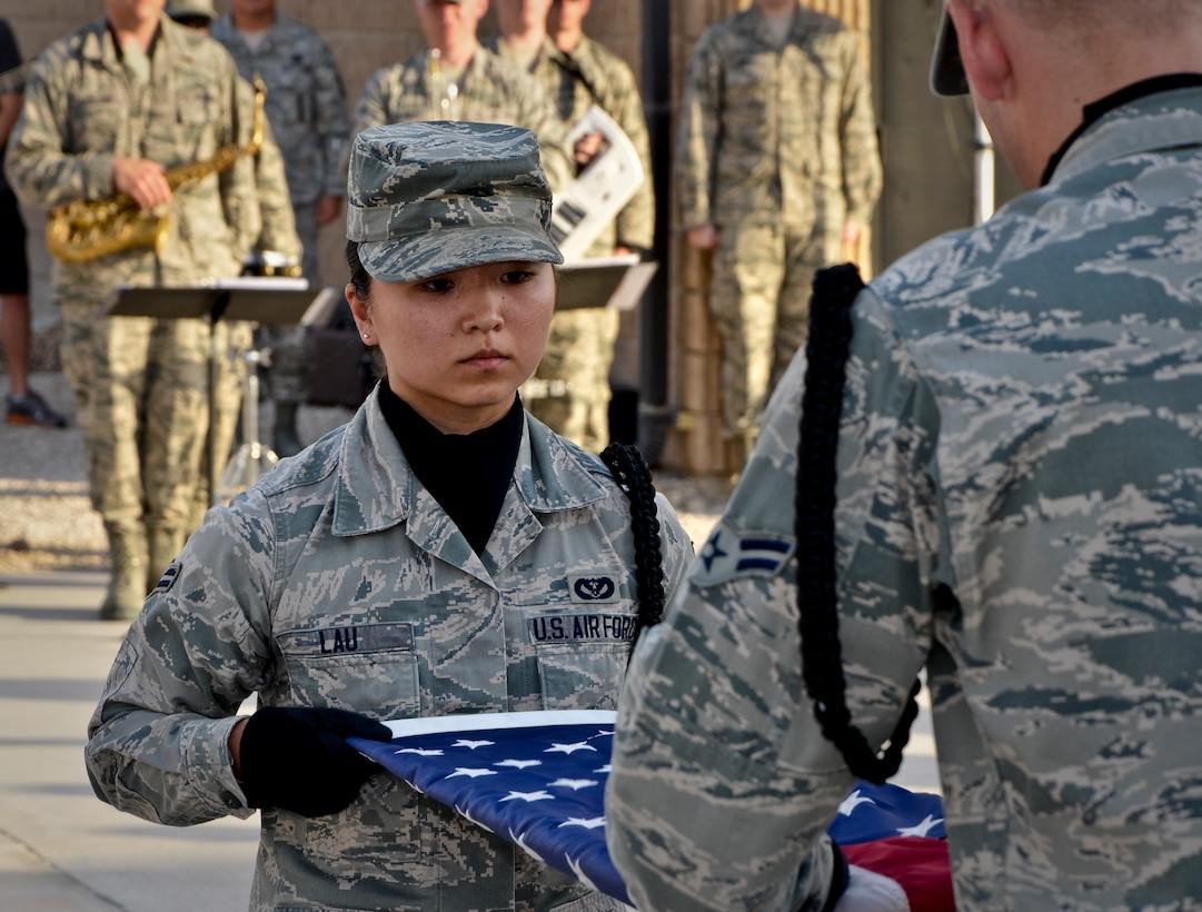 Airmen 1st Class Lena Lau and Justin Grahn fold the American flag during a Memorial Day retreat ceremony, May 27, 2013, at Memorial Plaza in Southwest Asia. Lau and Grahn are members of the 379th Air Expeditionary Wing honor guard. Military retreat ceremonies serve a twofold purpose: to signal the end of the official duty day and to pay respect to the U.S. flag. (U.S. Air Force photo/Senior Airman Benjamin Stratton)