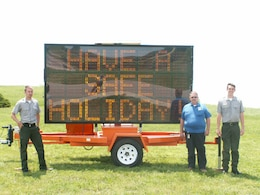 Water safety rangers Travis Sipe (Melvern Lake) and Lance Caldwell (Pomona Lake) pose with Bryce Romine, the Osage County Emergency Management director, in front of a highway control sign promoting safety during the Memorial Day weekend. Photo by James D. Franz.