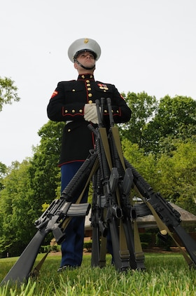 Lance Cpl. Michael Noyes, a rifle bearer with Marine Corps Base Quantico's ceremonial platoon, stands guard over a rifle stack prior to the Potomac Region Veterans Council Memorial Day Ceremony at Quantico National Cemetery on May 27, 2013. The day, originally called Decoration Day, is a day of remembrance for those who have died in service to our nation.
