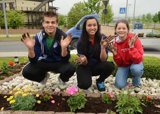 SPANGDAHLEM AIR BASE, Germany -- Kenny Love from Pensacola, Fla.; Mariel Munji from Pacifica, Calif.; and Abigail Cole from Vancleave, Miss.; volunteered to aid in a base beautification project May 18, 2013. Members from the Spangdahlem community came together in an effort to provide Spangdahlem AB with fresh flowers during current fiscal hardships. (U.S. Air Force photo by Airman 1st Class Kyle Gese/Released)
