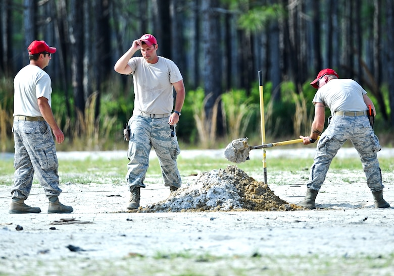 U.S. Airmen from 823rd Rapid Engineer Deployable Heavy Operational Repair Squadron Engineers, dig a hole before demolition training on Hurlburt Field, Fla., May 17, 2013. RED HORSE is known as a self-sufficient civil engineer response force capable of rapidly deploying to support contingency and special operations worldwide.  (U.S. Air Force photo/Airman 1st Class Christopher Callaway)