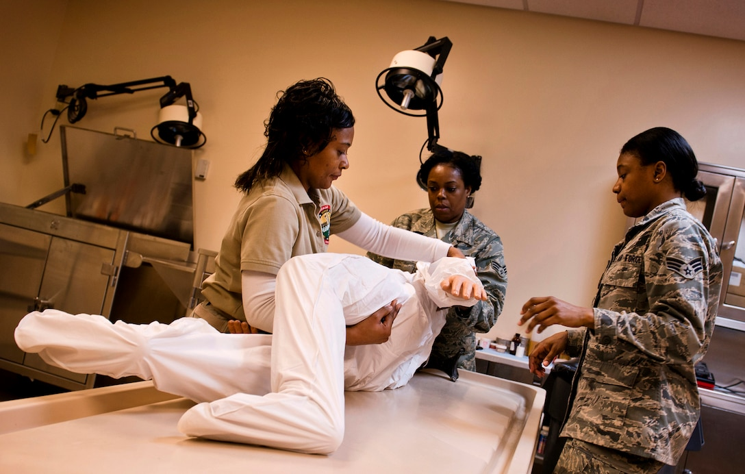 Mable Justice teaches Senior Airmen Tameca Burnett and Myisha Rufus the proper procedures of a full-body wrap at Dover Air Force Base, Del. The ultimate goal of the Air Force Mortuary Affairs Office morticians is to make the remains of fallen service members viewable. If that can't take happen, they use a full wrap technique and place the remains in the uniform requested by the family. (U.S. Air Force photo/Senior Airman Andrew Lee)