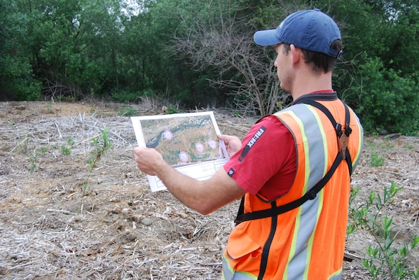 Alex Fromer, a biologist for RECON Environmental, Inc., checks a map on May 17 showing the locations of least Bell's vireo nests along the San Luis Rey River. Crews watering newly-planted native vegetation and spraying exotic plants in the area use the maps to avoid impacts on nesting vireos.