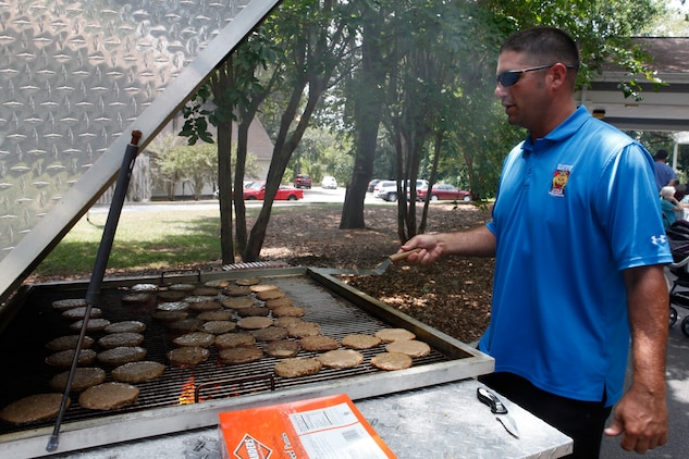 Brett Westerfield, Single Marine and Sailor Program coordinator, grills burgers during the program's visit to the River Oaks assisted living community, May 23. Each year, the SMP visits the assisted living community during Valentine's Day and Memorial Day weekend.