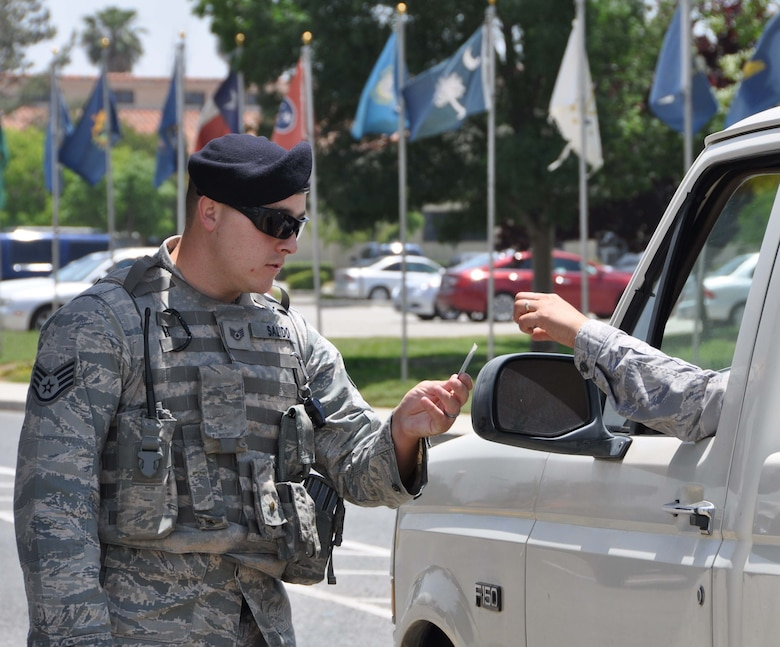 Staff Sgt. Adrian Salido, installation patrolman, 452nd Security Forces Squadron, checks the identification of a Team March member entering the main gate May 23, 2013. Salido is part of the team of SFS warriors who were recently awarded the 2012 Air Force Reserve Command Outstanding Security Forces Full-time Unit Award for their many outstanding unit and individual accomplishments. (U.S. Air Force photo/2nd Lt. Bari Yonkers)