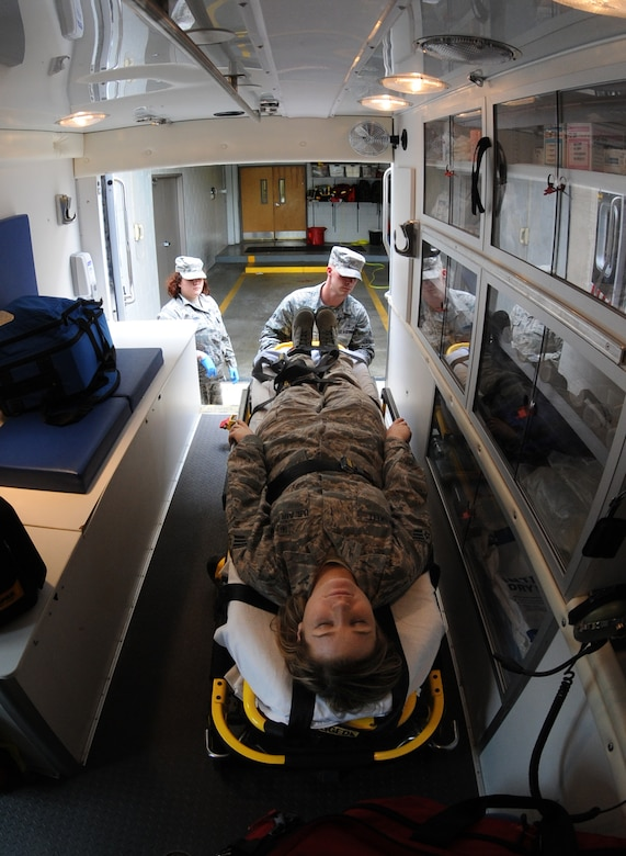 Senior Airman Blair Brakebill and Airman 1st Class Dillon Cobb, 509th Medical Operations Squadron ambulance services technicians, simulate placing a patient on a stretcher at Whiteman Air Force Base, Mo., May 29, 2013. Ambulance service technicians constantly train to ensure they are mission ready and fully qualified to complete the job. (U.S. Air Force photo by Airman 1st Class Bryan Crane/Released)