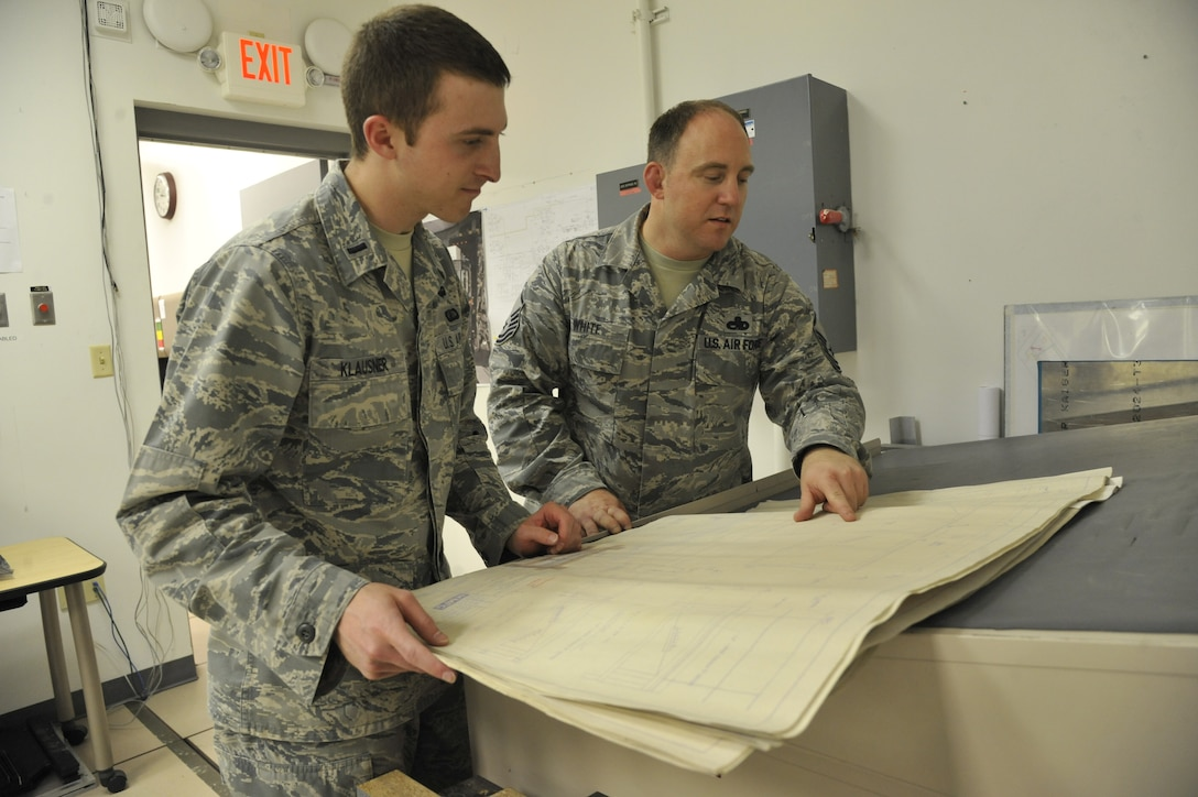 1st Lt. Andrew Klausner, 509th Maintenance Operations Squadron flight commander, and Master Sgt. Michael White, 509th MOS B-2 computer-aided design manager, review design drawings at Whiteman Air Force Base, Mo., May 15, 2013. The reviewing engineer ensures the drawings are accurate in building specifications for aircraft or tools. (U.S. Air Force photo by Airman 1st Class Keenan Berry/Released)