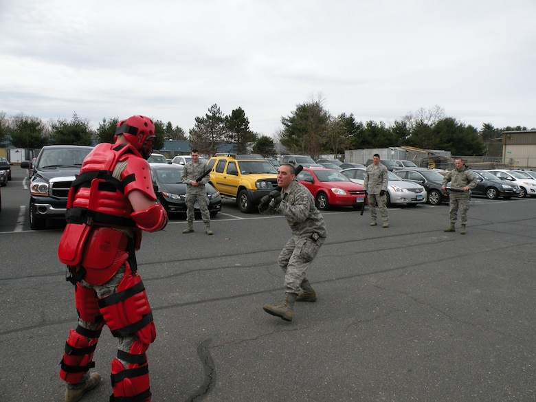 Senior Airman Marvin Perez of the 103rd Security Forces Squadron practices approaching a combative 'hostile' in a red man suit as part of a training exercise at Bradley Air National Guard Base, East Granby, Conn. in 2013. (Photos courtesy of Tech. Sgt. Jessica Roy)