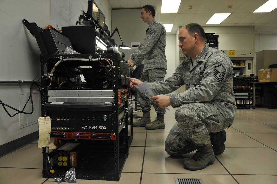 1st Lt. Andrew Klausner, 509th Maintenance Operations Squadron flight commander, and Master Sgt. Michael White, 509th MOS B-2 Spirit computer-aided design manager, perform an adaptable communications suite check on the Defense Advanced GPS Receiver at Whiteman Air Force Base, Mo., May 15, 2013. White is programming the DAGR for operation with the communications suite. (U.S. Air Force photo by Airman 1st Class Keenan Berry/Released)