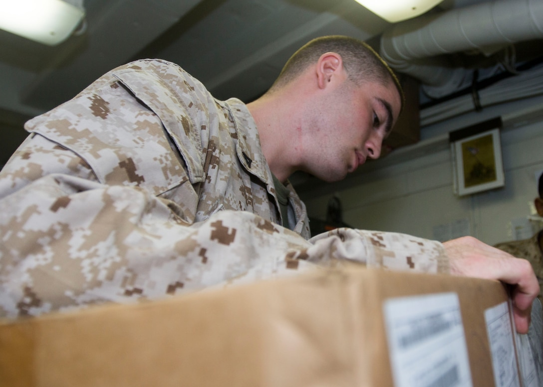 U.S. Marine Lance Cpl. Kenneth T. Mellan, a supply administrative specialist assigned to the 26th Marine Expeditionary Unit, closes a package after checking its contents aboard the USS Kearsarge (LHD 3) at sea, May 26, 2013. The 26th MEU is a Marine Air-Ground Task Force forward-deployed to the U.S. 5th Fleet area of responsibility aboard the Kearsarge Amphibious Ready Group serving as a sea-based, expeditionary crisis response force capable of conducting amphibious operations across the full  range of military operations. (U.S. Marine Corps photograph by Cpl. Kyle N. Runnels/Released)