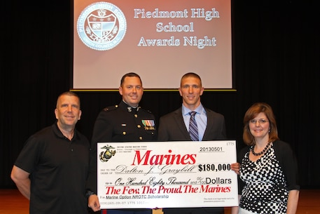 Capt. Peter C. Foster, the officer selection officer for Charlotte, N.C., presents a Naval Reserve Officers Training Corps Scholarship check to Dalton J. Graybill on May 28 at Piedmont High School. The NROTC scholarship, valued at up to $180,000, will pay for the cost of full tuition, books and other educational fees at many of the country's leading colleges and universities. (Marine Corps Photo by Sgt. Aaron Rooks)