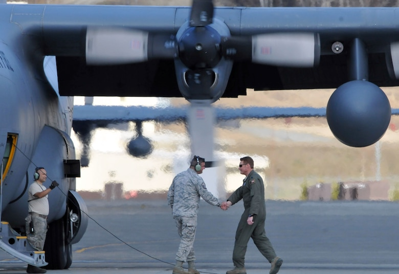 """JOINT BASE ELMENDORF-RICHARDSON, Alaska -- Lt. Col. Blake Gettys, commander of the 176 Operations Group, bids farewell to Master Sgt. Derek Netzly, a member of the Ohio Air National Guard's 179th Airlift Squadron and the new crew chief of C-130 cargo plane """"Five Four"""" here May 23, 2013. The """"Five Four"""" is one of three C-130s that were transferred from the Alaska Air National Guard's 176 Wing to the Ohio Air National Guard's 179th Airlift Wing. National Guard photo by Staff Sgt. N. Alicia Goldberger."""