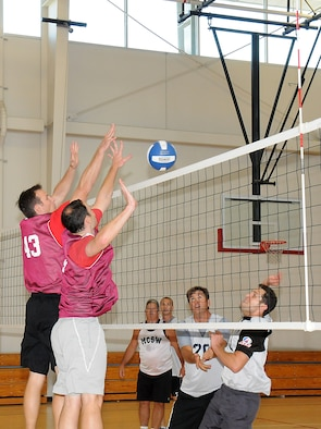 Players from SMC's Infrared Space Systems directorate volleyball team attempt to block a return shot from the MILSATCOM team during a playoff game, May 30. The MILSATCOM team won the match for the overall volleyball championship. (Photo by Joe Juarez)
