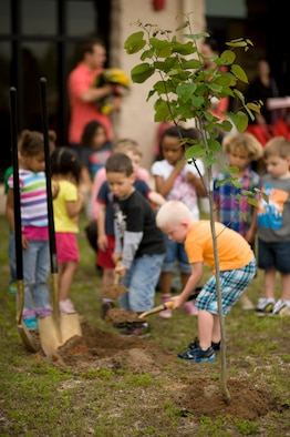 Children from the Hurlburt Field Child Development Center East help during a tree planting ceremony at the CDC East at Hurlburt Field, Fla., April 24, 2013.  Tree planting helps minimize erosion, provides wind breaks and cuts cooling and heating costs. (U.S. Air Force Photo/Senior Airman Hayden K. Hyatt)