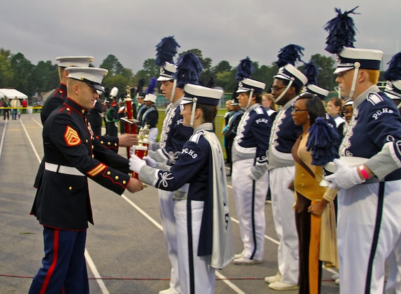 U.S. Marine Corps Staff Sgt. William Niepert, left, the staff noncommissioned officer in charge of Recruiting Sub-Station Newport News, Recruiting Station Richmond, and a native of Mulberry Grove, Ill., presents trophies to representatives of the Pasquotank County High School Panthers Marching Band, from Elizabeth City, N.C., at the Kempsville Classic Band Review, Oct. 19, 2013. Thirteen high school marching bands competed in the event, showcasing their musical and marching talents in field shows with varied themes and were judged by music educators in showmanship, musicality, marching and more. The Marine recruiters took time to congratulate every band on their outstanding performances and educate them on the musical opportunities in the Marine Corps' Musician Enlistment Option Program. (U.S. Marine Corps photo by Cpl. Aaron Diamant/Released)