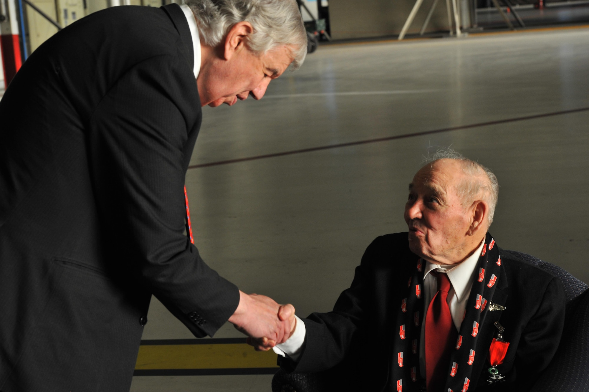 Jack Cowan of Honorary Consul of France shakes hands with retired Maj. Clarence Grimes Oct. 25, 2013, at Fairchild Air Force Base, Wash. The 92-year old was honored with the highest recognition by the French government for his contributions almost 70 years ago to defend and preserve the independence of France.