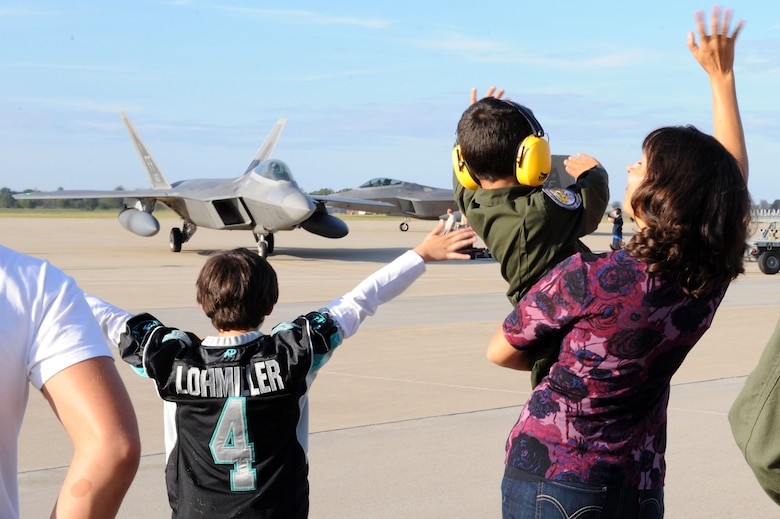 Family members wave to returning service members of the 27th Fighter Squadron Oct. 18, 2013, at Langley Air Force Base, Va.. More than 300 Airmen deployed in support of Pacific Command theater security package rotation to Kadena Air Base, Japan. While on deployment 27th FS pilots and maintainers integrated with the U.S. Navy and Japanese Self Defense Force.