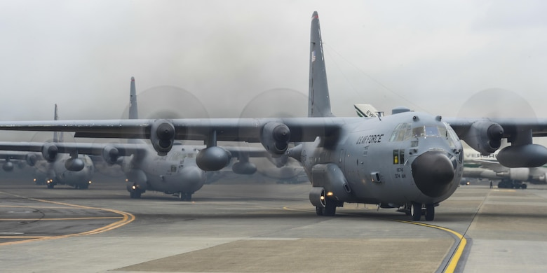 Ten C-130 Hercules aircraft taxi on a runway during a large formation mission Oct. 22, 2013, at Yokota Air Base, Japan.  The C-130s flew toward the Aomori region, testing Yokota AB's capability to launch aircraft and assist anywhere in the Western Pacific region.