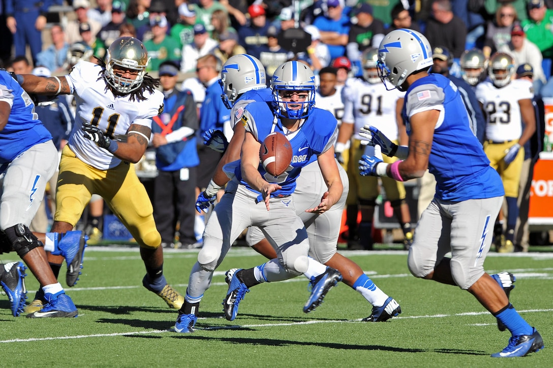 U.S. Air Force Academy freshman quarterback, Nate Romine, pitches to wide receiver, Sam Gagliano, during the Air Force-Notre Dame game Oct. 26, 2013, at Falcon Stadium in Colorado Springs, Colo. The game marked Romine's first start as quarterback for Air Force.