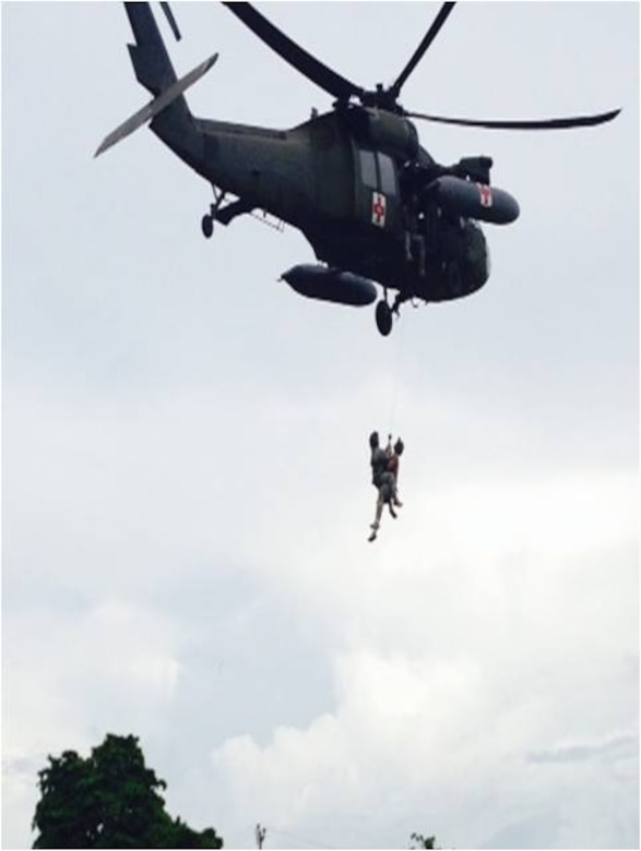 """U.S. Army Capt. Christopher Morisoli and Warrrant Officer Dylan Kovenz, both pilots assigned to the 1-228th Aviation Regiment, Joint Task Force-Bravo, hold a HH-60 Blackhawk helicopter at a high hover while U.S. Army Staff Sgt. Matthew Reed, flight medic, is hoisted up by U.S. Army Staff Sgt. Kyle Farnes during a live hoist training exercise in Puerto Castilla, Honduras, Oct. 30, 2013.  The 1-228th's """"C"""" Company teamed up with Special Boat Team 22 as well as Honduran soliders to conduct the training.  (Photo by U.S. Army 1st Lt. Michael Pierce)"""