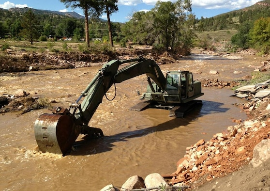 A military hydraulic excavator works to clear the remainder of a Colorado road after a flood washed it away. Many roads were destroyed during the Colorado flood leaving some Colorado residences stranded and forced to backpack in fuel and food to their homes. (File Photo by DART-W Public Affairs Office, 36th Infantry Division)