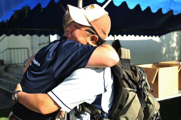 U.S. Air Force Senior Master Sgt. Robert Miller, 909th Aircraft Maintenance Unit superintendant, embraces Tech. Sgt. Makoto Mizuguchi, a Japan Air Self-Defense medical technologist from Naha Hospital during the 14th annual Kadena Special Olympics on Kadena Air Base, Japan, Nov. 2, 2013.  Mizuguchi volunteered his medical ambulance services during the KSO event in the event of a medical emergency. (U.S. Air Force photo by Staff Sgt. Amber E. N. Jacobs)