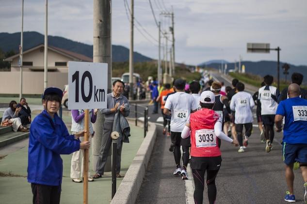 Hagi Iwami Airport Half Marathon participants run past the 10-kilometer marker during the race Oct. 20, 2013. The race consisted of a half marathon, 10-kilometer and two-kilometer portion.