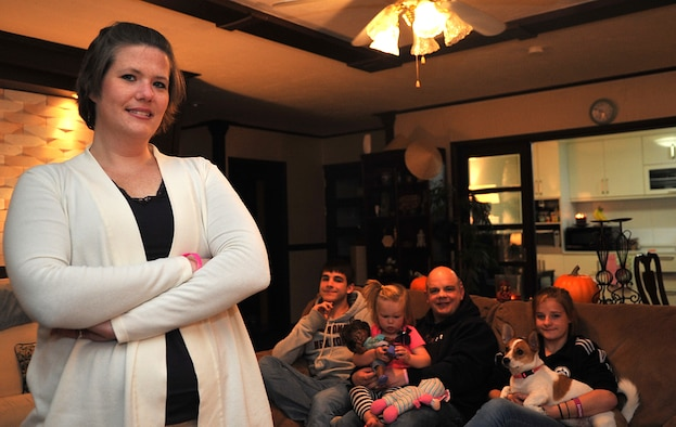 Katie Hampton, foreground, Osan Middle School special education teacher and breast cancer survivor, stands with her family, Master Sgt. Mike Rawlins, middle right, 7th Air Force fuels war planner, and their children, Andrew, 17, Abigale, 2, and Erin, 16, at their home in Pyeongtaek-si, Republic of Korea, Oct. 30, 2013. Hampton credits her victory over cancer to the love and strength she was able to draw from her immediate family and extended family in the U.S., as well as from friends and coworkers. (U.S. Air Force photo/Airman 1st Class Ashley J. Thum)