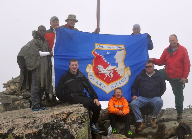 Members of the 157th Aircraft Maintenance Squadron pose for a photo during the annual Flags On The 48 event, Bond Cliff, Lincoln New Hampshire Sept. 14, 2013.   The event is a memorial hike to commemorate 9/11.  Pictured left to right: Senior Airman Sterling Howard, Chief Master Sgt. Scott Taatjes, Lt. Col. Adam Shattuck, Senior Airman Christopher Ager, Steven Shattuck, Lisa Rogers (a hiker from Manchester, N.H.) Tech. Sgt. John Seguin, and Master Sgt. Richard Blais. (Courtesy photo Richard Blais)