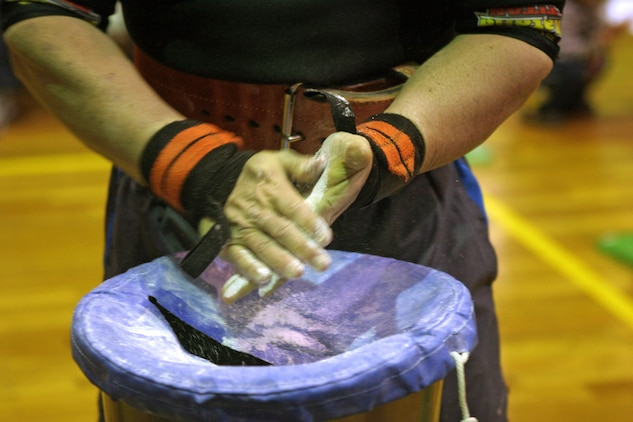 Abe Roman, the overall 2012 open bench press competition winner, coats his hands in chalk in preparation for a lift during the 2012 open bench press competition here Jan. 21. The chalk helps to keep competitors hands dry so the weight does not slip from their hands during the crucial part of a lift.