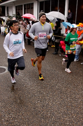 Victor T. Delaflor, a station runner, jogs with Japanese runners during the 6th annual Kintai Road Race near the Kintai Bridge Sunday. More than 2,200 running enthusiasts, including more than 30 Marines, sailors and station residents, competed in a unique cultural experience between two athletic cultures.