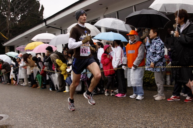 Joseph A. Pacentrilli, a station runner, is cheered on by spectators during the 6th annual Kintai Road Race near the Kintai Bridge SundayMore than 2,200 running enthusiasts, including more than 30 Marines, sailors and station residents, competed in a unique cultural experience between two athletic cultures.