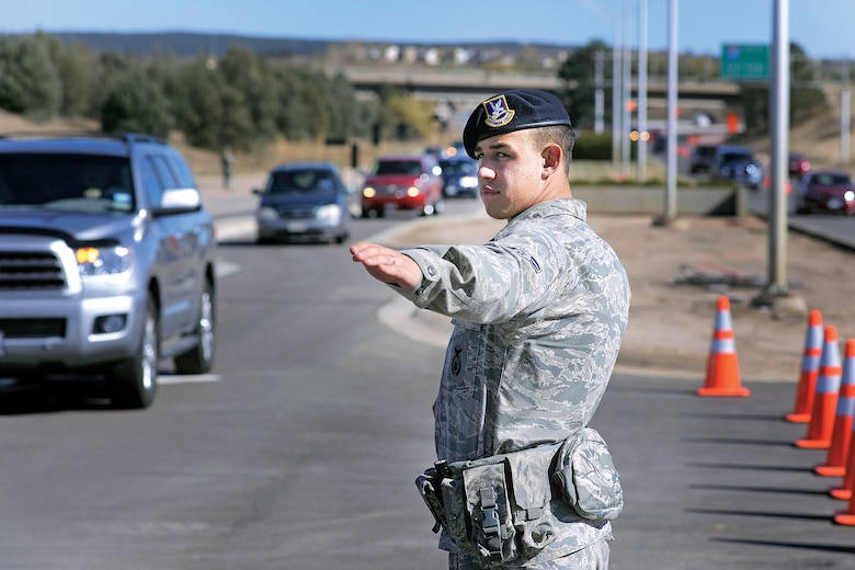 A 10th Security Forces Squadron Airman directs traffic through the Academy's north gate to Falcon Stadium for the Air Force vs. Notre Dame football game Oct. 26, 2013. Providing a safe route of travel to the stadium is just one of the many ways security forces Airmen here serve and protect Falcon fans and the U.S Air Force Academy on game day.