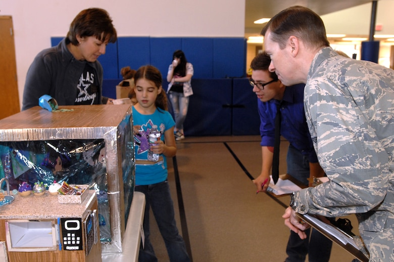 Victor Correa from WDAZ and Col. Christopher Mann, 319th Air Base Wing vice commander, listen as Aeryn Power explains about her cardboard fish aquarium Nov. 2, 2013, at the 2013 Global Cardboard Challenge at Liberty Square on Grand Forks Air Force Base, N.D. Correa and Mann were part of a judges panel, along with Pete Haga, assistant to Grand Forks Mayor Michael Brown, who judged each of the competitors' entries. Aeryn won in the age 5-8 category for her creation. (U.S. Air Force photo/Staff Sgt. Susan L. Davis)