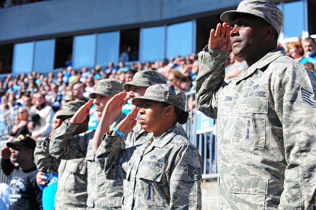 """Service members in the """"Row of Honor"""" render salutes during the National Anthem at Bank of America Stadium in Charlotte, N.C., Nov. 3, 2013. Five Airmen from Seymour Johnson Air Force Base were selected by the USO of North Carolina Panthers as special guests for their selfless service to their country. (U.S. Air Force photo by Airman 1st Class John Nieves Camacho)"""