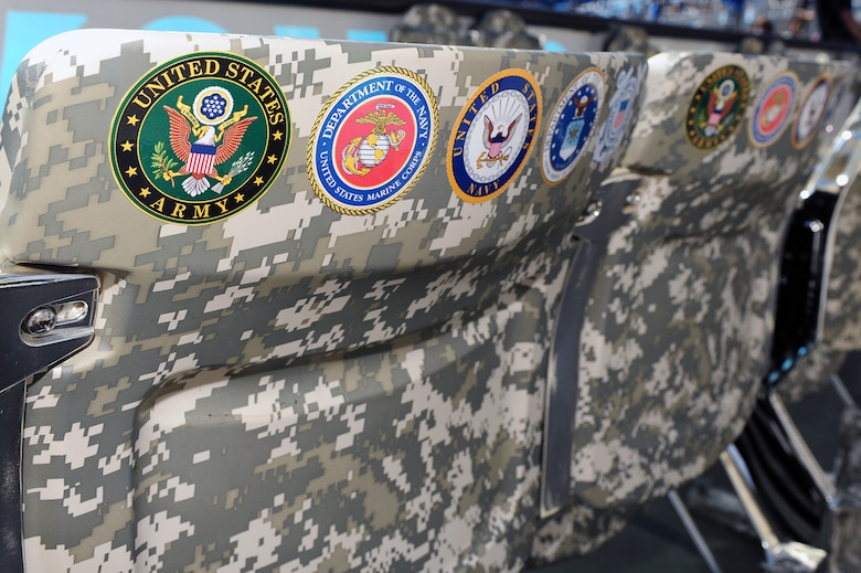 """The """"Row of Honor"""" was created by the National Football League to pay tribute to Service members by treating them to a free football game. The """"Row of Honor"""" contains eight seats, seven of which are designed in camouflage and decorated with the seals of the military service branches, and one blacked-out chair dedicated to POW/MIAs. These seats were most recently filled by five members of Team Seymour during a Carolina Panthers game in Charlotte, N.C., Nov. 3, 2013. (U.S. Air Force photo by Airman 1st Class John Nieves Camacho)"""