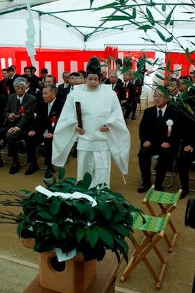 An Iwakuni City Shirasaki Shrine priest walks to her seat during the purification and blessing of the Iwakuni Kintaikyo Airport ground breaking ceremony here Nov. 25. The priests asked the Shinto God and local guardian spirits to bless and protect the construction workers as they build the new air terminal.