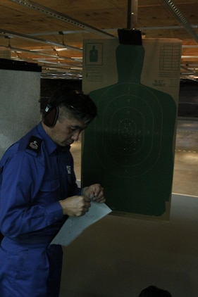 Japanese Maritime Self-Defense Force Petty Officer 1st Class Hiroshi Nagashima, a Fleet Air Wing 31 air crewman, posts a fresh target for the next shooter during rifle re-qualification and familiarization training at the Indoor Small Arms Range here Dec. 2. The sailors shot in groups of six at a time.