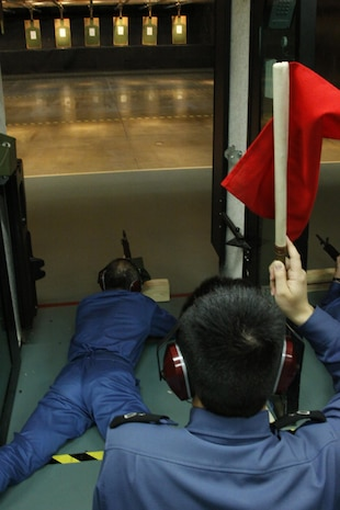 A Japanese Maritime Self-Defense Force sailors snap into the prone position and aim down range while another JMSDF sailor holds a red flag in the air during rifle re-qualification and familiarization training at the Indoor Small Arms Range here Dec. 2. Red flags were used to notify the range coach who still had live rounds.