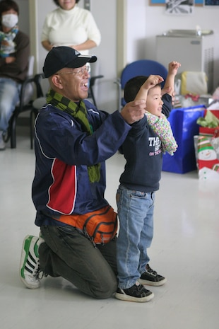 A Japanese volunteer helps a small child from the Akibono Orphanage lead fellow children in singing their school song during an on-base visit to the Robert M. Casey Medical and Dental Clinic here Saturday. The purpose was to allow the children to join in the camaraderie of American and Japanese service members spreading holiday cheer.