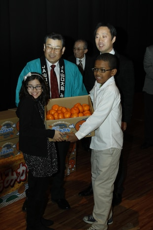 Matthew C. Perry Elementary School student counsel members display Mikan fruit with Motoi Yoshimura, Yamaguchi Oshima Agricultural Cooperative Association president and Yoshihiko Fukudo, Iwakuni City mayor during the 2nd annual Mikan Exchange at the Sakura Theater here Dec. 15. A Mikan is a small fruit simialr to a tangerine.